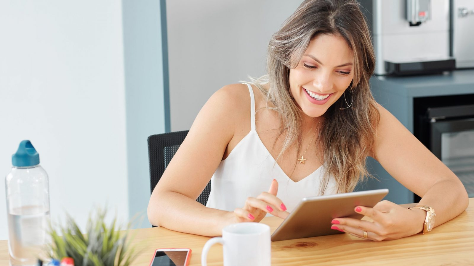 Beautiful smiling young business lady answering e-mails on tablet computer