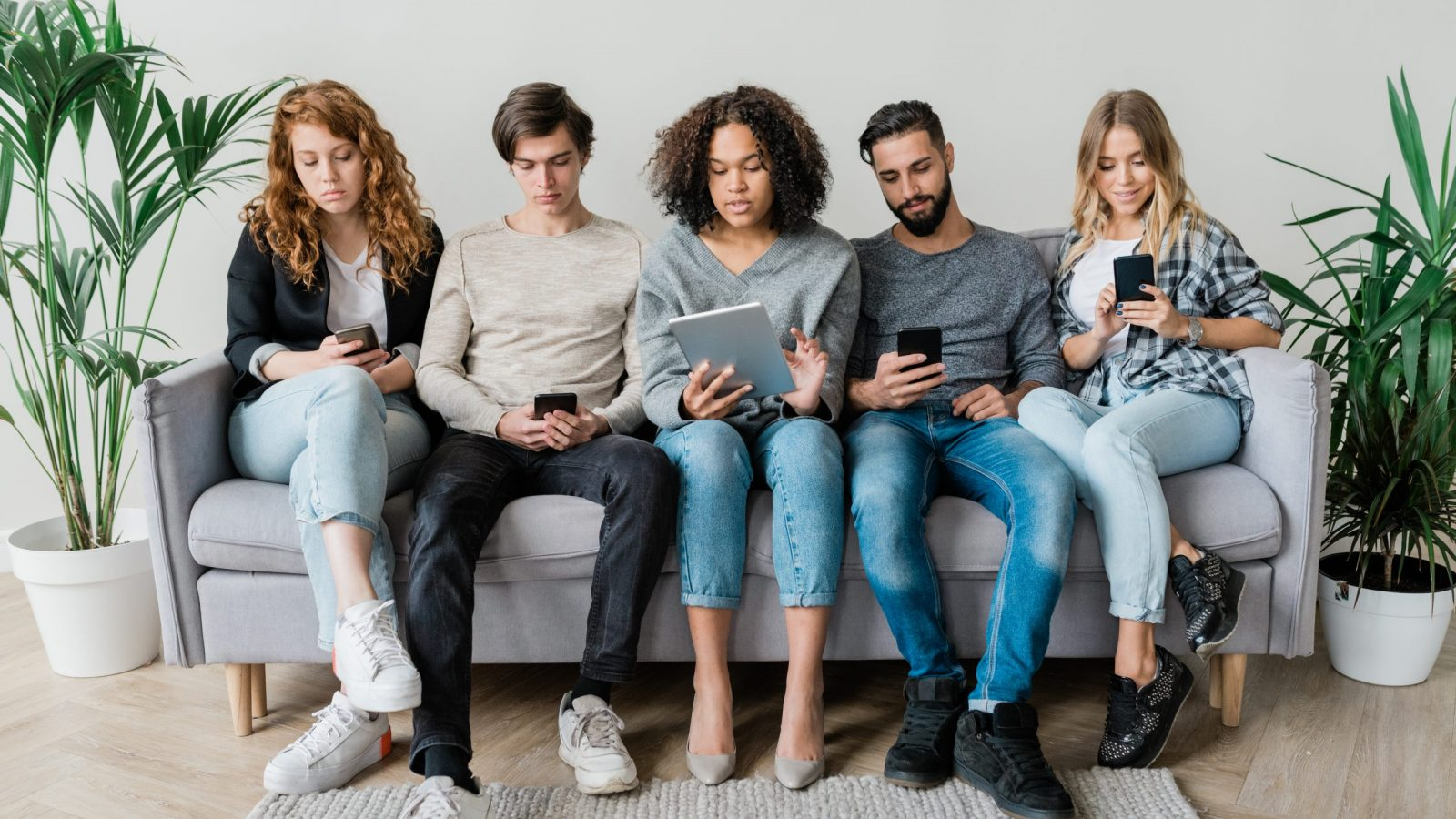 Five young contemporary casual friends sitting on couch in row by wall while using mobile gadgets
